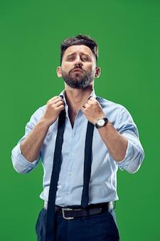 남성 뷰티 개념. 녹색 배경 위에 포즈 유행 양복을 입고 세련된 머리를 가진 유행 젊은이의 초상화. 완벽한 머리카락. 우아한 이탈리아 스타일.