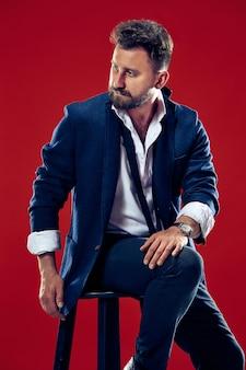 붉은 벽 위에 포즈 유행 양복을 입고 세련된 헤어 스타일 유행 젊은이의 남성 뷰티 개념 초상화