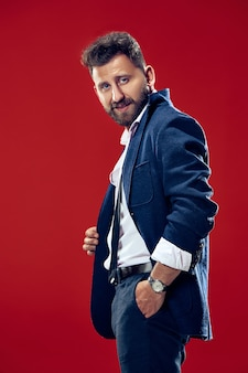 Концепция мужской красоты. портрет модного молодого человека со стильной стрижкой в модном костюме