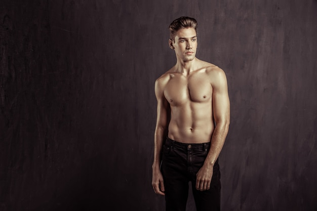 Male beauty. handsome well built man looking aside while standing without a t shirt
