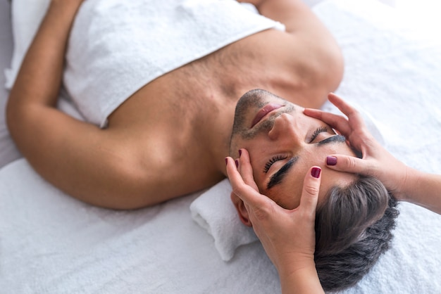 Male beauty - man receiving facial massage at luxury spa