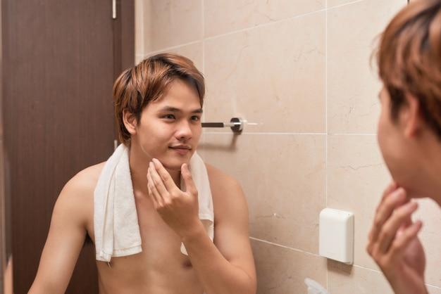 男性の美しさ。剃った後、彼の滑らかな顔に触れる若いハンサムなアジア人