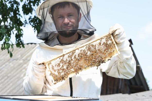 보호복을 입은 남성 양봉가는 초심자를 위한 벌집과 벌집을 가지고 있습니다