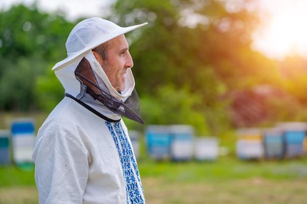 じんましんの背景の上の男性の養蜂家。保護帽子。背景がぼやけている。蜂蜜とミツバチ。