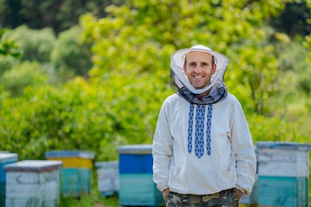 Мужской пчеловод на фоне ульев. защитная шапка. размытый фон. мед и пчелы.