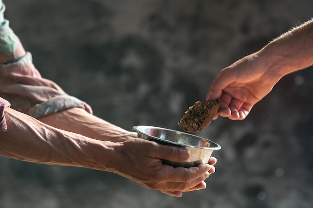Male beggar hands seeking food or money with coins tin from human kindness on the wooden