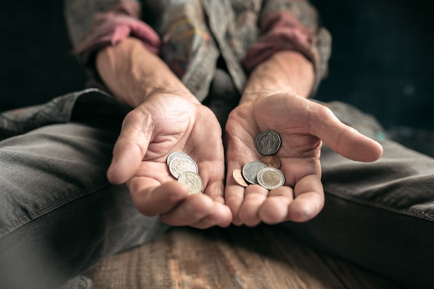 남자 거지 손은 공공 길이나 거리 산책로에서 나무 바닥에 돈, 인간의 친절에서 동전을 찾고 있습니다. 도시에서 노숙자 가난한입니다. 재정 문제, 거주지.