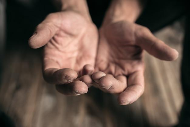 公共の小道の木製の床でお金を求めている男性の乞食の手