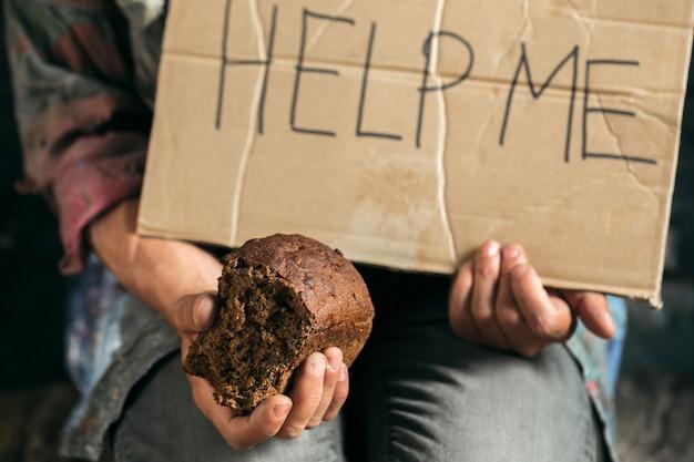 남자 거지 손은 공공 길이나 거리 보도에 있는 나무 바닥에 인간의 친절로부터 도움을 요청하는 사인으로 돈을 찾고 있습니다. 도시에서 노숙자 가난한입니다. 재정 문제, 거주지.