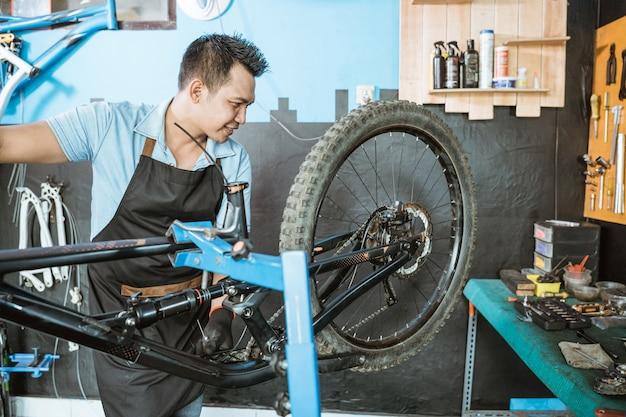 문제를 해결하는 동안 프리웰의 기능을 확인하는 앞치마를 입은 남성 자전거 정비사