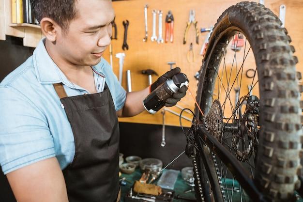 윤활제 스프레이를 적용하는 동안 병을 들고 앞치마에 남성 자전거 정비사