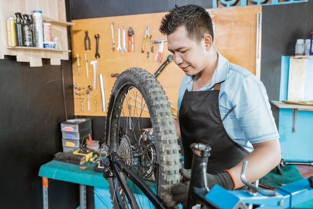 앞치마를 입은 남성 자전거 정비사는 문제를 해결하는 동안 바퀴를 조입니다