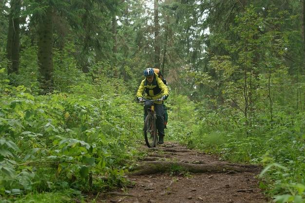 男性の自転車観光客が山の秋の森で木の根で未舗装の小道を登る