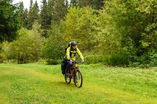 가을 숲을 통해 남성 자전거 관광 타기