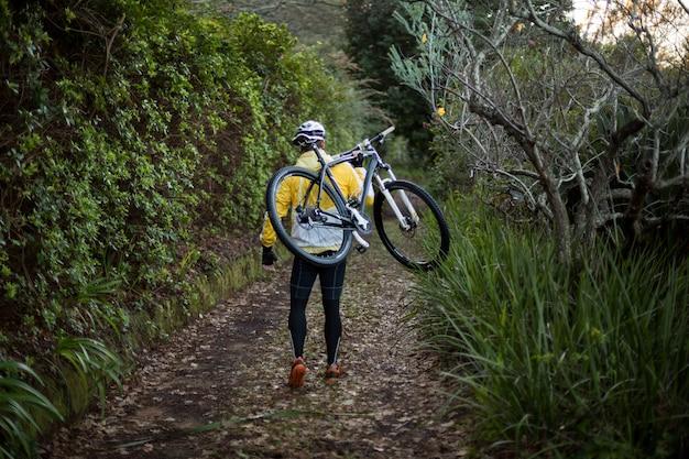 Male biker carrying mountain bike and walking on dirt track