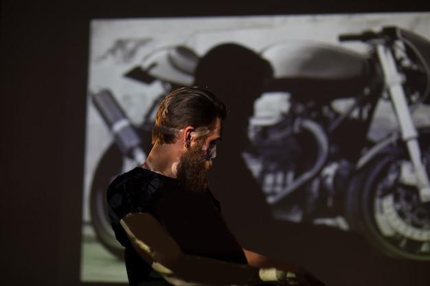 Мужчина-байкер, стоящий на фоне фотографии своего мотоцикла. концепция хобби