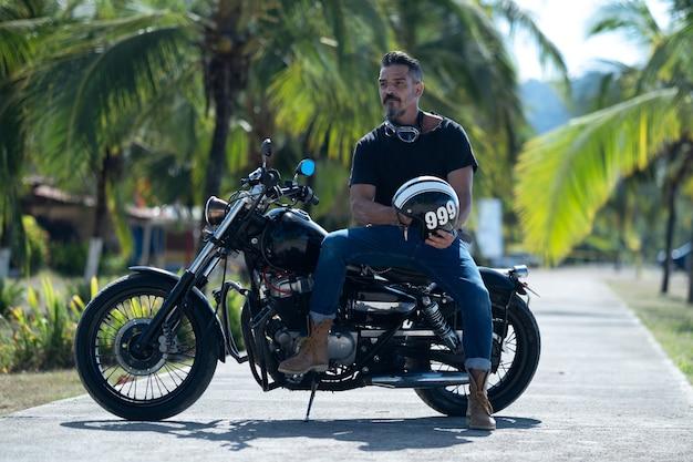 두꺼운 수염을 기른 남성 바이커가 아름다운 공원에서 오토바이를 타고 포즈를 취하고 있다