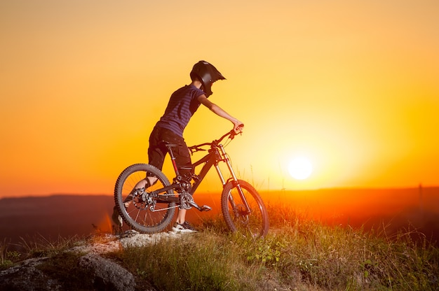 Male biker with mountain bicycles on the top of hill against evening sky with bright sun at the sunset