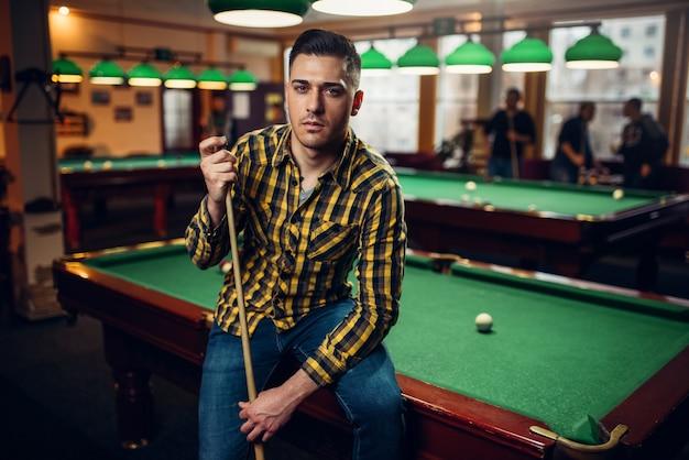 緑のテーブルでキューポーズの男性ビリヤードプレーヤー。