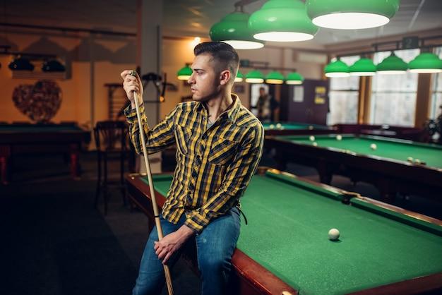 テーブルでのキューのポーズを持つ男性ビリヤードプレーヤー