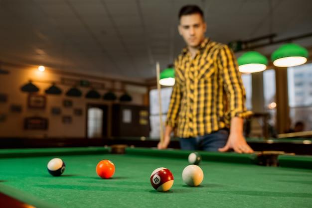 キューを持つ男性ビリヤードプレーヤー、カラフルなボールを持つテーブルからの眺め
