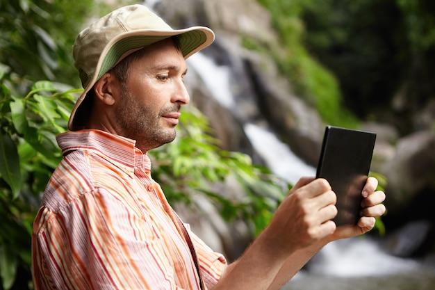Биолог-мужчина в полосатой рубашке и шляпе работает в природном парке, фотографирует или записывает на видео дикую природу, используя свой черный цифровой планшет, стоящий на фоне водопада и зеленых деревьев