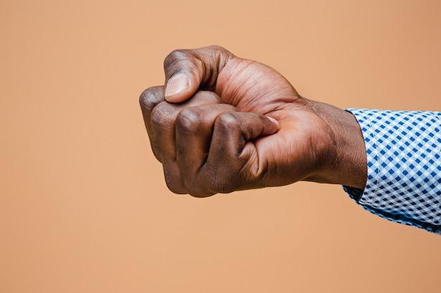 Pugno nero maschio isolato su marrone. mano serrata afroamericana, gesticolando