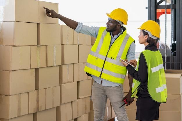 젊은 아시아 여성 감독관이 창고 공장에서 함께 문서를 확인하는 동안 남성 흑인 노동자가 판지 상자를 가리키고 있다