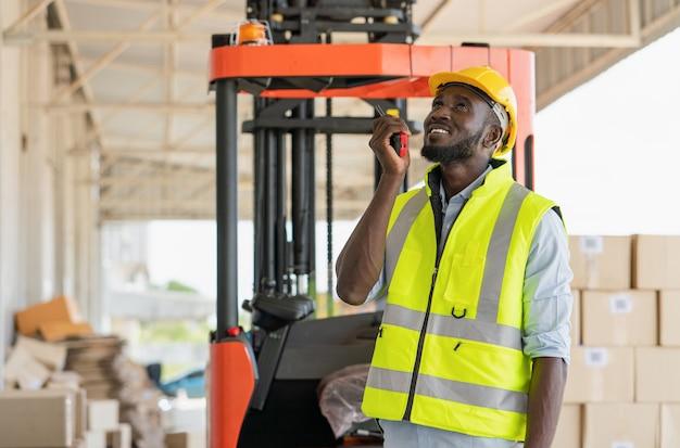 창고 공장에서 운송을 위해 판지 상자에 상품을 준비하는 동안 무전기를 사용하여 작업을 명령하는 남성 흑인 노동자