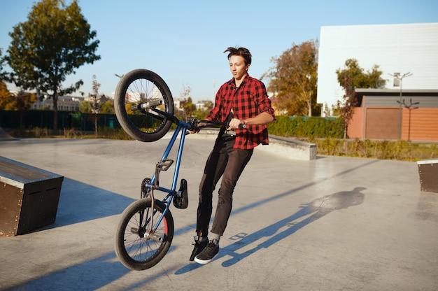 Байкер мужского пола делает трюк, тренируется в скейтпарке. экстремальный велосипедный спорт, опасные велотренировки, риск-стрит, езда на велосипеде в летнем парке
