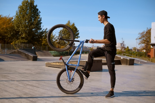 Байкер мужского пола делает трюк, тренируется в скейтпарке. экстремальный велосипедный спорт, опасные велотренировки, рискованная уличная езда