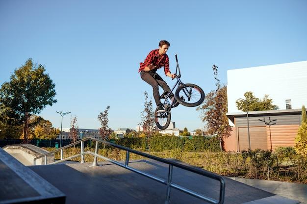 Байкер мужчина bmx, прыжок в действии, подросток на тренировке в скейтпарке. экстремальный велосипедный спорт, опасные велотренировки, риск-стрит, езда на велосипеде в летнем парке