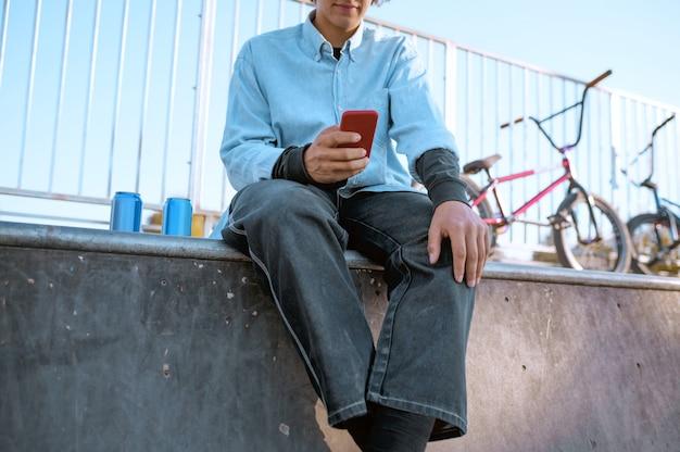 Мужчина-байкер bmx отдыхает на рампе в скейтпарке после тренировки. экстремальный велосипедный спорт, опасные велотренировки, уличная езда, езда на велосипеде в летнем парке