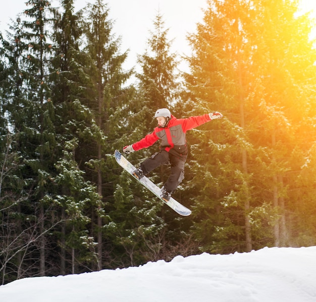 Male boarder jumping and keeps one hand on the snowboard
