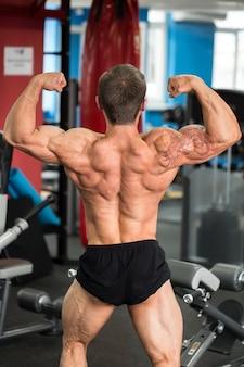 上腕二頭筋を曲げる男性のボディービルダー、背面図