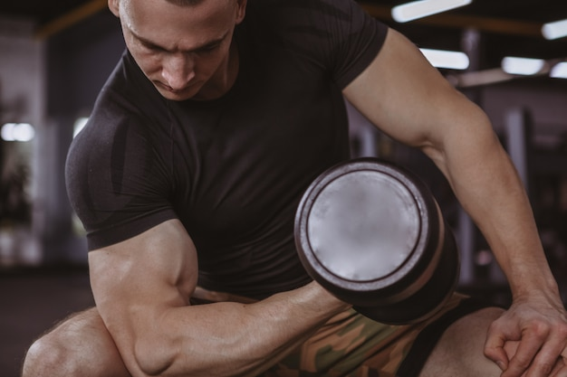 Male bodybuilder lifting dumbbells at the gym