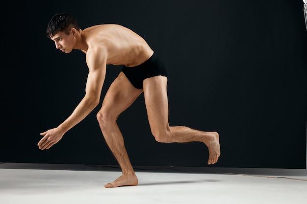 Обнаженное мускулистое тело мужского культуриста в черных трусиках позирует в студии