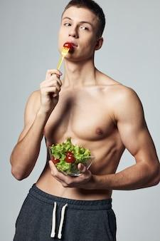男性のボディービルダーのサラダのトップレスプレート健康的な食事