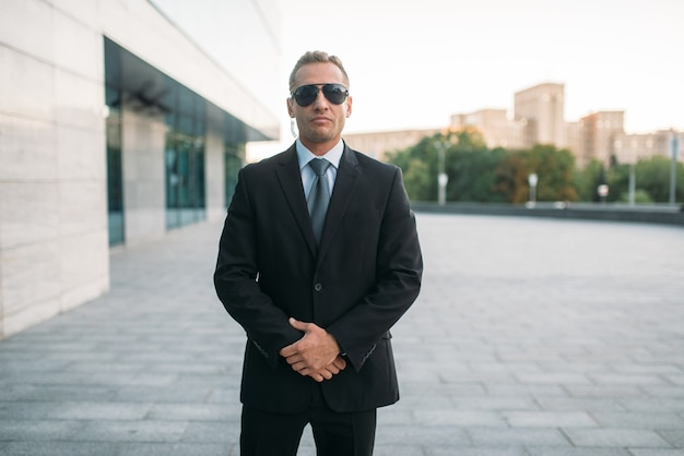 Male bodyguard in suit, security earpiece and sunglasses outdoors.