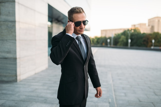Male bodyguard in suit and sunglasses talking by security earpiece  outdoors. professional guarding is a risky profession