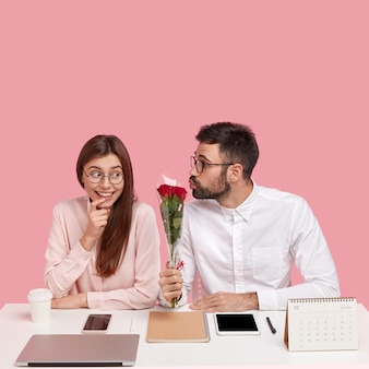 Male boss fell in love with young pretty colleague, gives beautiful red roses, folds lips for making kiss, happy lady receives compliment and flowers, sits at desktop in office against pink wall