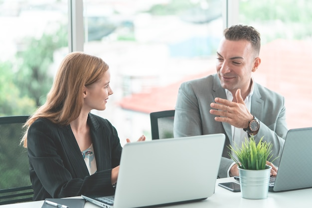 Male boss is discussing with female worker in happy manner