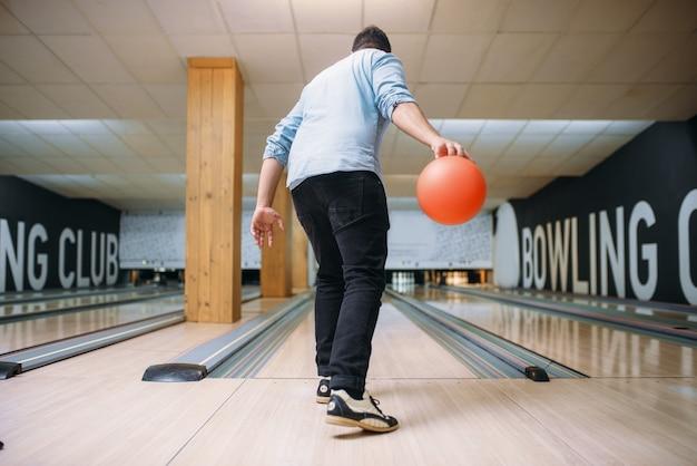 レーンに立ってボールでポーズをとる男性ボウラー