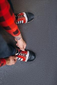 男性ボウラーが家の靴に靴ひもを結ぶ
