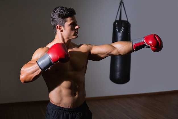 Male boxer attacking with his left in health club
