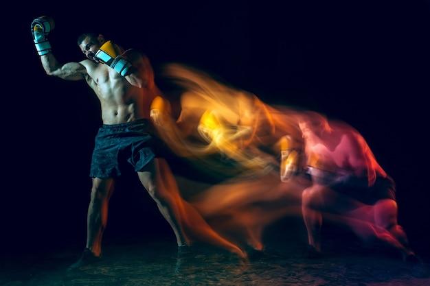 Мужской боксер бокс в темной студии. коллаж с одной кавказской моделью. движение стробоскопа, движение, действие. подходит молодой спортсмен на черном фоне тренажерный зал