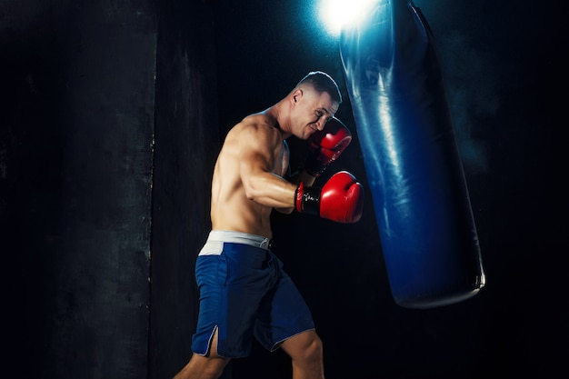 Male boxer boxing in punching bag with dramatic edgy lighting