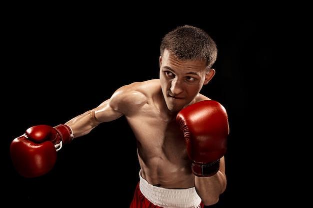 Boxer maschio boxe con drammatica illuminazione tagliente in uno studio buio