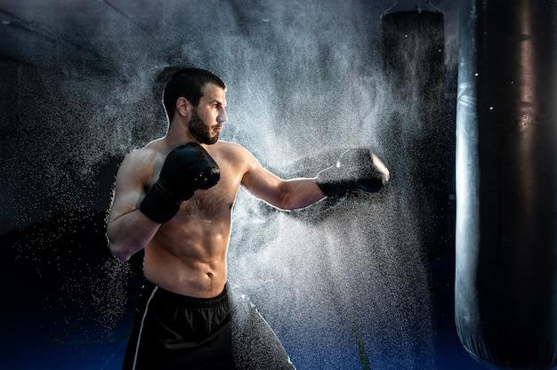 Боксер-мужчина бьет огромную боксерскую грушу в боксерской студии. человек боксер обучение трудно. фото высокого качества