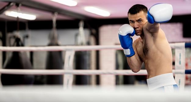 Мужской боксер тренируется на ринге